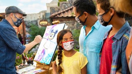 Integrantes de una familia sonríen mientras observan a un artista pintar un cuadro de Mickey Mouse