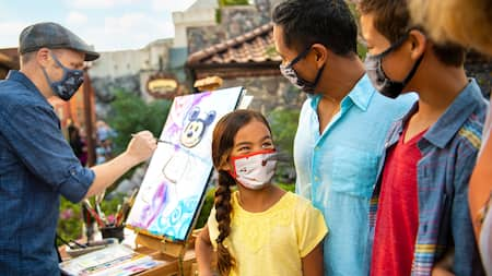 A family smiles as they watch an artist paint a picture of Mickey