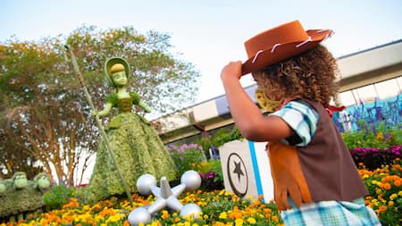 A girl tips her hat towards a topiary of Bo Peep from Toy Story