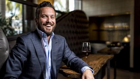 O Chef Fabio Viviani sorri sentado em um sofá com uma taça de vinho tinto