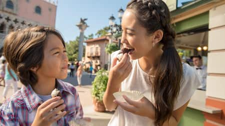 A mother and her son eat cannoli at the Italy Pavilion in World Showcase