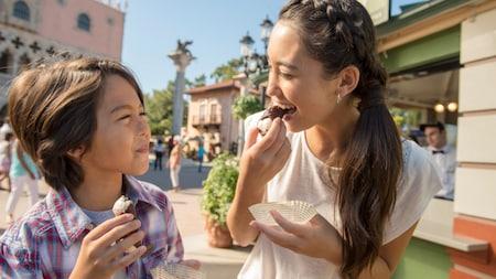 Mãe e filho saboreiam um cannoli no Pavilhão da Itália na World Showcase