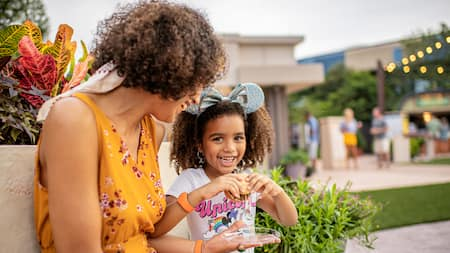 Mom and young daughter sit and eat at Epcot Festival Booth