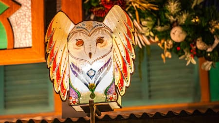 A large Christmas ornamental owl high over a street at the park