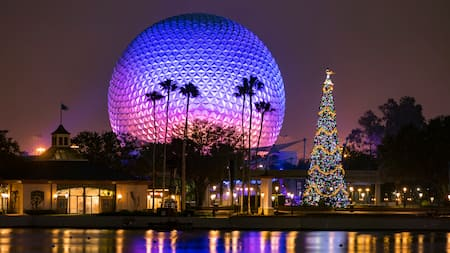 The iconic Spaceship Earth lit up at night with the lagoon in the forefront glistening from the lights and a large fully decorated Christmas tree