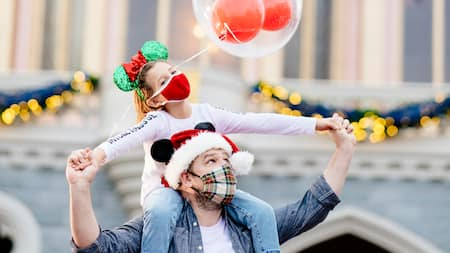 Dad and Daughter wear holiday gear in front of Cinderella Castle