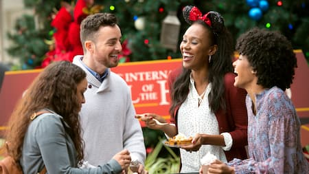 Four adults eating desserts stand in a group in front of a Christmas tree at Epcot