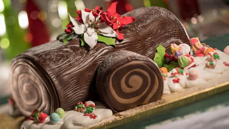 A yule log decorated with festive flowers and small figurines of gingerbread men and candy canes