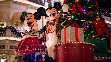 Con atuendos festivos, Mickey Mouse y Minnie Mouse saludan frente a un árbol de Navidad