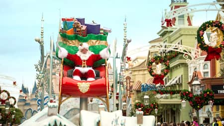 Santa Claus rides down festive Main Street U S A in a big sleigh filled with gifts
