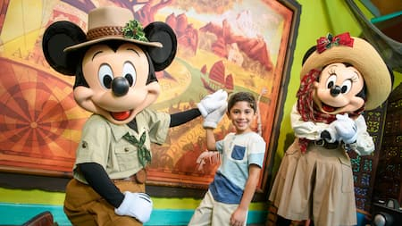 Mickey Mouse con un acebo en su sombrero y Minnie con un moño y una bufanda festiva mientras saludan a un niño pequeño