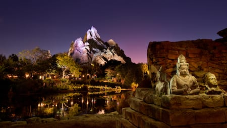 Asian statues next to Discovery River with snow-capped Mt. Everest in the background at night
