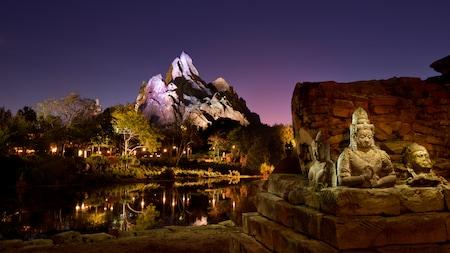Estatuas asiáticas junto al río Discovery River con el pico nevado del monte Everest de fondo por la noche