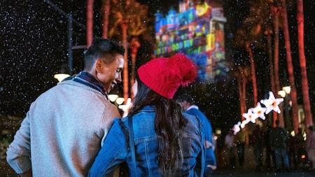 Una pareja mira palmeras y un edificio cubierto con luces festivas