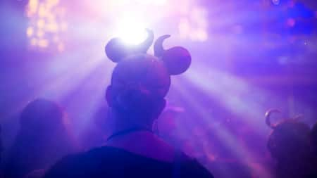 A woman wearing Ursula inspired Mickey Mouse Ears looks out on a crowd