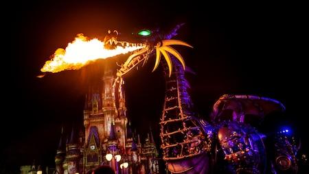 Una carroza de un dragón que expulsa fuego por la boca pasando junto a Cinderella Castle por la noche