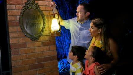 A couple and their 2 kids stand by a sign on a brick wall that reads The Haunted Mansion as the dad holds a lantern