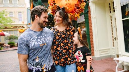 Una joven familia de 3 personas con atuendos de Halloween sonríen en Walt Disneyland World Resort