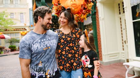 Uma jovem família de 3pessoas usando roupas de Halloween da Disney e sorrindo uns para os outros no Walt Disneyland World Resort