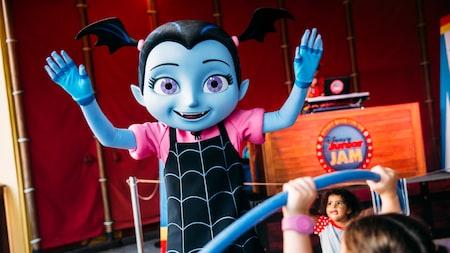 Vampirina se tient debout, les bras levés, près d'une enseigne indiquant «Disney Junior Jam»