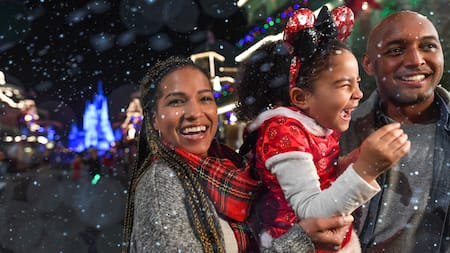 Um casal segurando a filha com neve caindo na Main Street USA no Magic Kingdom Park
