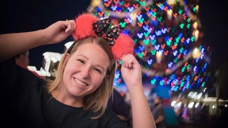 Une femme portant des oreilles de Minnie Mouse devant un arbre de Noël