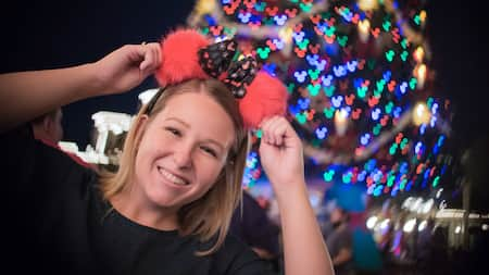 A woman wearing Minnie Mouse ears in front of a Christmas tree