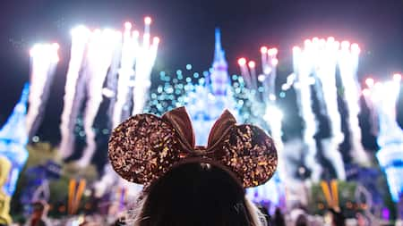 A girl wearing Minnie Mouse ears watching fireworks burst around Cinderella Castle