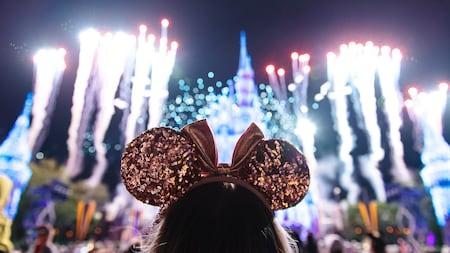 Une fille portant des oreilles de Minnie Mouse regarde des feux d'artifice exploser autour du Cinderella Castle