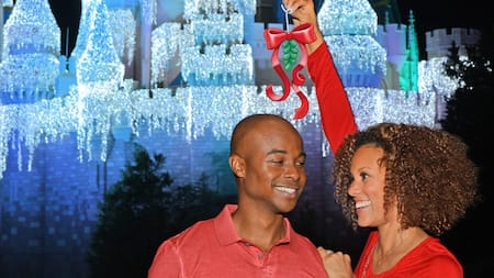 A woman holds a mistletoe over a man while standing in front of an illuminated Cinderella Castle