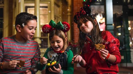 Três crianças alegres vestidas em trajes natalinos compartilham sobremesas com a neve caindo ao seu redor
