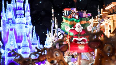 A smiling Santa Clause sits on his sleigh, surrounded by his reindeer and Cinderella Castle