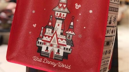 """Uma bolsa tote estilo de supermercado com um desenho de um castelo decorado para as festas de fim de ano e os dizeres """"Walt Disney World"""""""