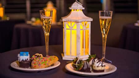 2 plates with treats and 2 flutes of champagne next to a decorative lantern