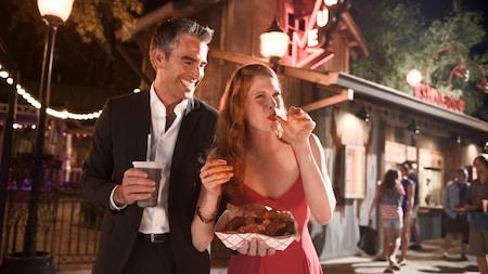 Una pareja con atuendos elegantes disfruta una bebida en Disney Springs