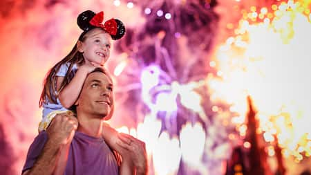 A happy little girl with Minnie Ears watches a fireworks display from atop her dads shoulders