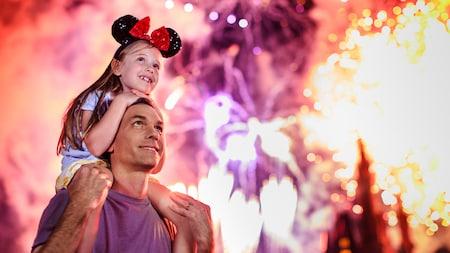 Una niña feliz con orejas de Minnie mira un espectáculo de fuegos artificiales sentada en los hombros de su padre