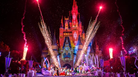 Fireworks stream into the air around Cinderella Castle, which is awash in colored lighting