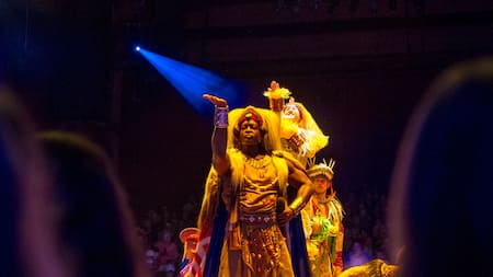 Spirited dancers pose on stage during the Festival of the Lion King show