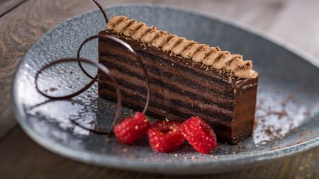 A piece of chocolate cake near 3 raspberries and a twist of chocolate