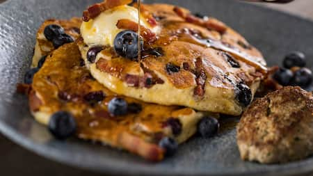 A hand pours syrup on a blueberry bacon pancake, served with a sausage patty on the side