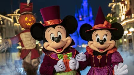 Mickey Mouse and Minnie Mouse pose in formal Halloween attire with a scarecrow in the background