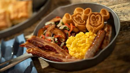 A cast iron skillet loaded with bacon, sausage, scrambled eggs, Mickey Mouse waffles and country potatoes, all next to a tray with biscuits and gravy