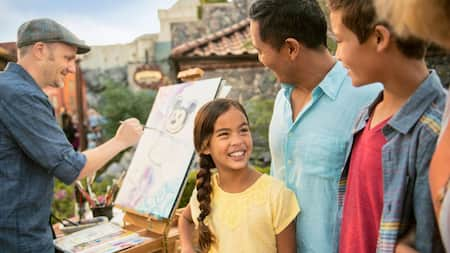 3miembros de una familia joven sonríen mientras observan a un artista pintar un cuadro de Mickey Mouse