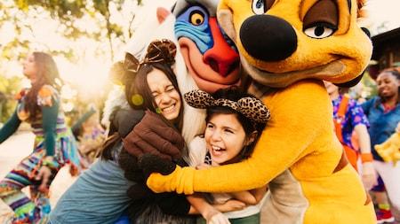 Los Personajes Timon y Rafiki de The Lion King abrazan a 2niñas sonrientes en el Parque Temático Disney's Animal Kingdom
