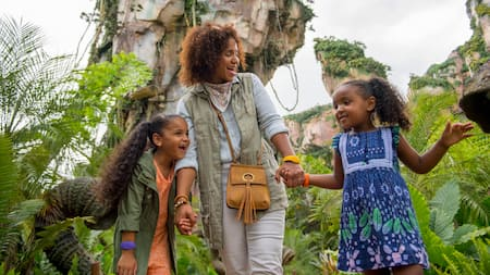 A woman shares a laugh with her daughters, walking through an alien jungle