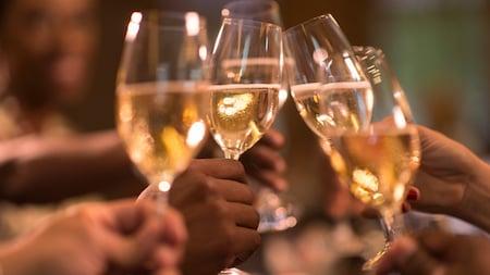 Plusieurs mains rapprochent des verres de vin blanc pour porter un toast
