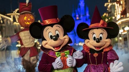 Mickey Mouse y Minnie Mouse posando con atuendos formales de Halloween, con un espantapájaros en segundo plano