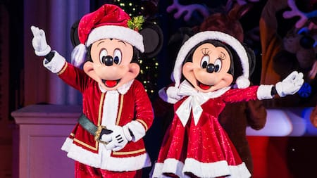 Mickey and Minnie pose, waving, in Santa Claus holiday outfits