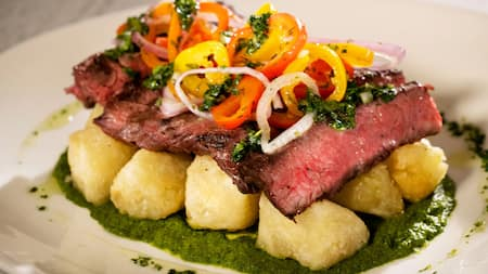 Steak topped with peppers, onions and herbs resting on a bed of potatoes and sauce